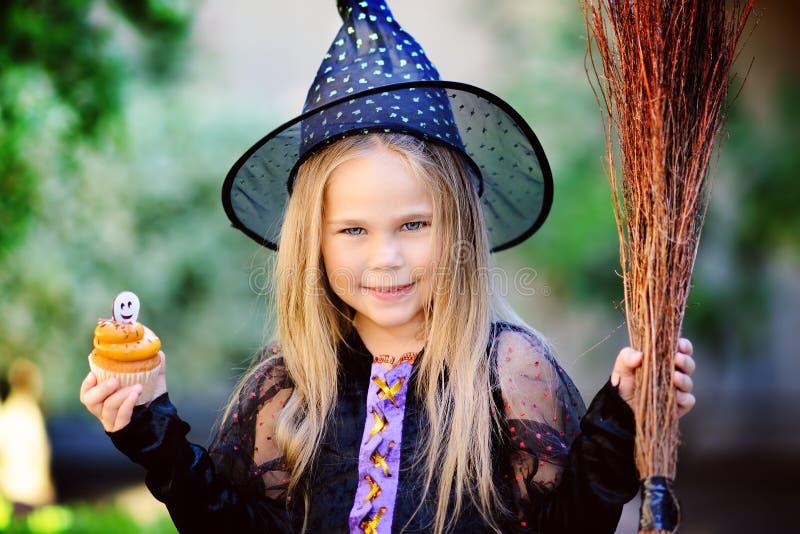 巫婆服装的女孩在万圣夜吃杯形蛋糕 免版税库存照片