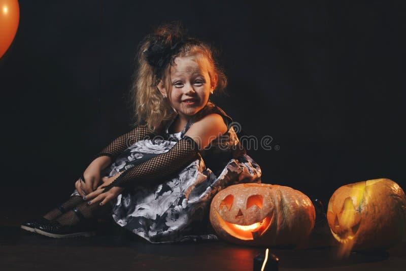 巫婆服装的滑稽的儿童女孩为万圣夜用南瓜杰克和在黑暗的木背景的橙色气球 库存图片