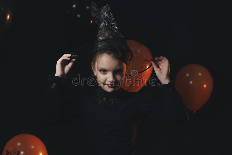 巫婆服装的滑稽的儿童女孩为万圣夜用南瓜杰克和在黑暗的背景的橙色气球 免版税库存图片