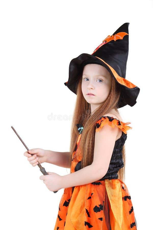 巫婆橙色服装的女孩为万圣夜拿着鞭子 免版税库存图片