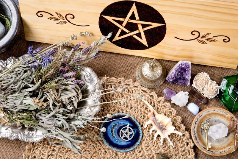 巫婆法坛装饰-与五芒星形、草本和水晶,与自然小钩黄麻法坛布料 库存照片