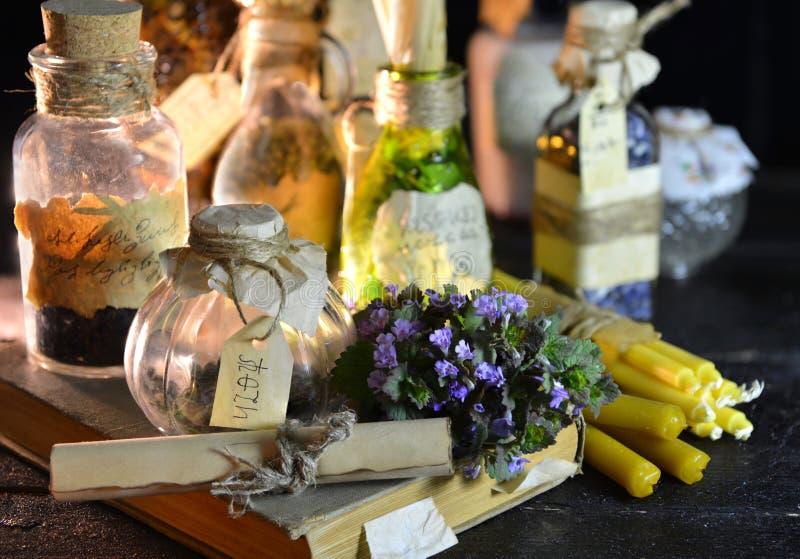 巫婆瓶、草本和蜡烛,不可思议的静物画 库存照片