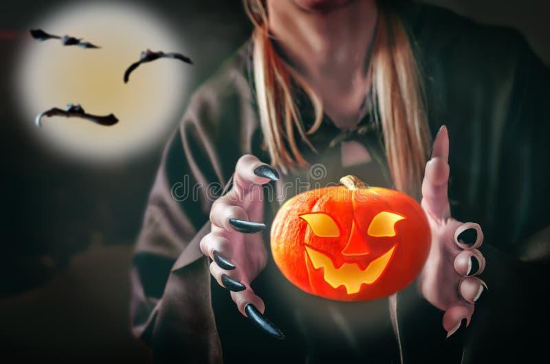 巫婆` s手用在黑暗的背景的一个飞行发光的南瓜 免版税图库摄影