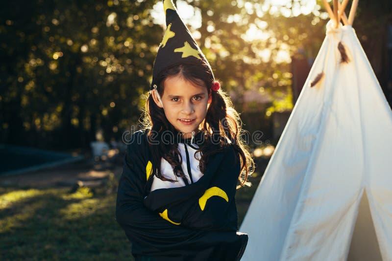 巫术师服装的逗人喜爱的女孩 库存图片