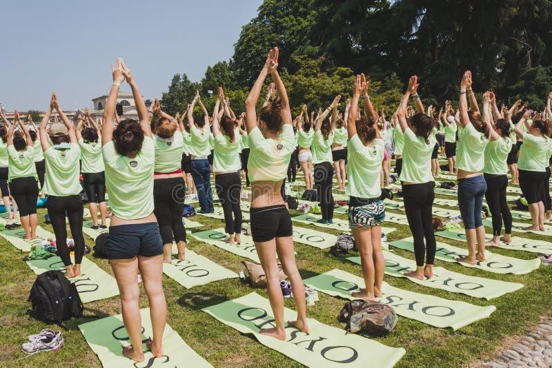 差不多2000个人在一个城市公园上自由集体瑜伽课在米兰,意大利 免版税图库摄影