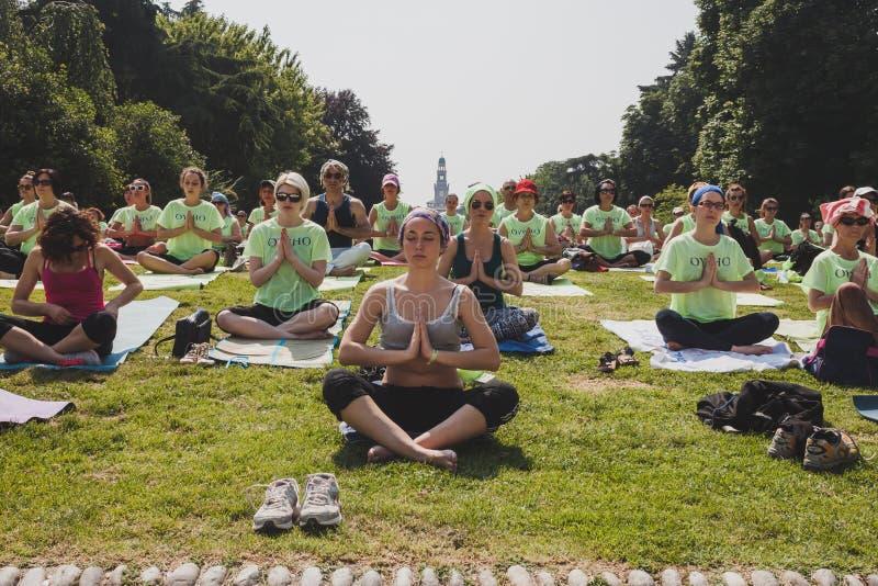 差不多2000个人在一个城市公园上自由集体瑜伽课在米兰,意大利 免版税库存照片