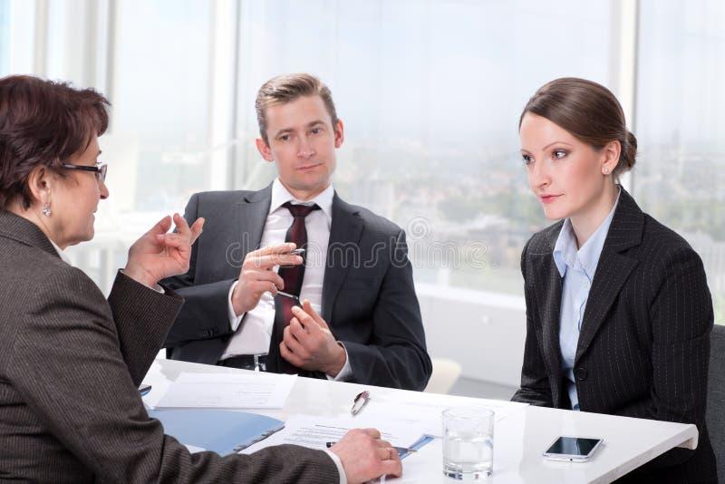 已婚夫妇咨询一位成熟妇女律师 免版税库存照片