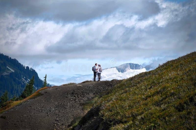 已婚的年轻人夫妇远足在山 免版税图库摄影