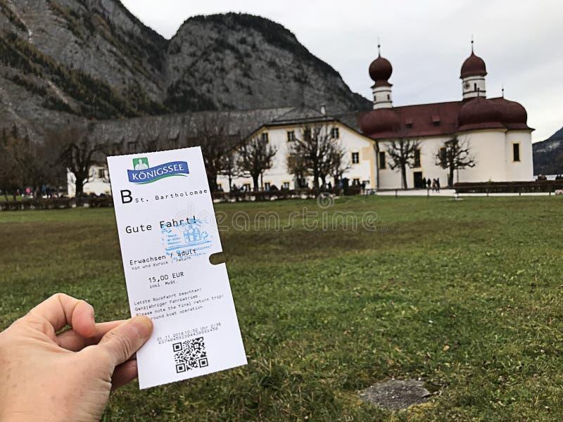 已经被盖印了StBartholomew的教会不加考虑表赞同的人Konigsee湖小船旅行的票 库存图片
