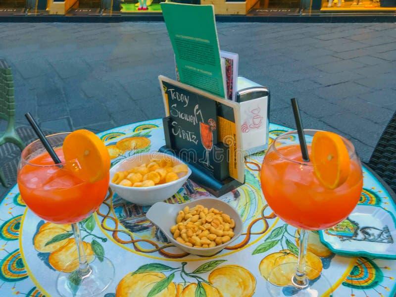 巴勒莫西西里岛意大利2018年6月26日:两块玻璃Aperol在意大利喷在一张陶瓷桌上的鸡尾酒在一个街道咖啡馆 免版税库存照片