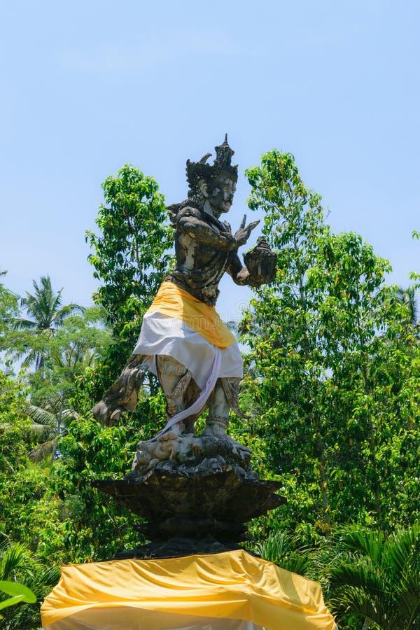巴厘岛印度尼西亚 2018年10月6日 用在天空蔚蓝和绿色树前面的裙子报道的传统巴厘岛神雕塑 免版税图库摄影