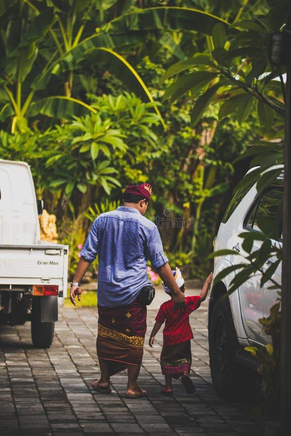 巴厘岛,印度尼西亚- 2018年4月13日:与他的父亲的亚洲孩子在巴厘语婚礼之日 印度尼西亚孩子 免版税库存照片