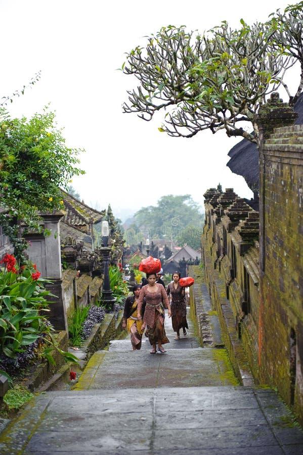 巴厘岛,印度尼西亚- 2011年2月23日:未认出的巴厘语人民在传统礼服走在2011年2月23日的Pura Besakih 图库摄影