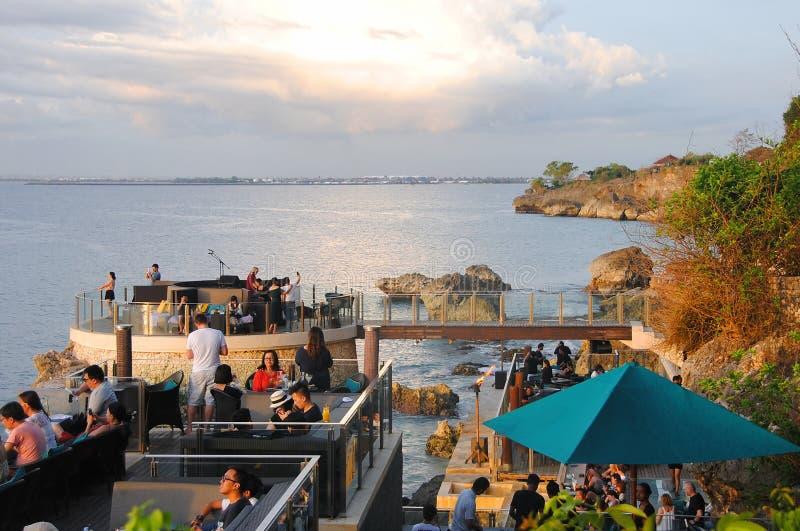 巴厘岛/印度尼西亚- 2017年1月7日:人观看的日落和有饮料在著名岩石酒吧在巴厘岛,印度尼西亚 免版税库存照片
