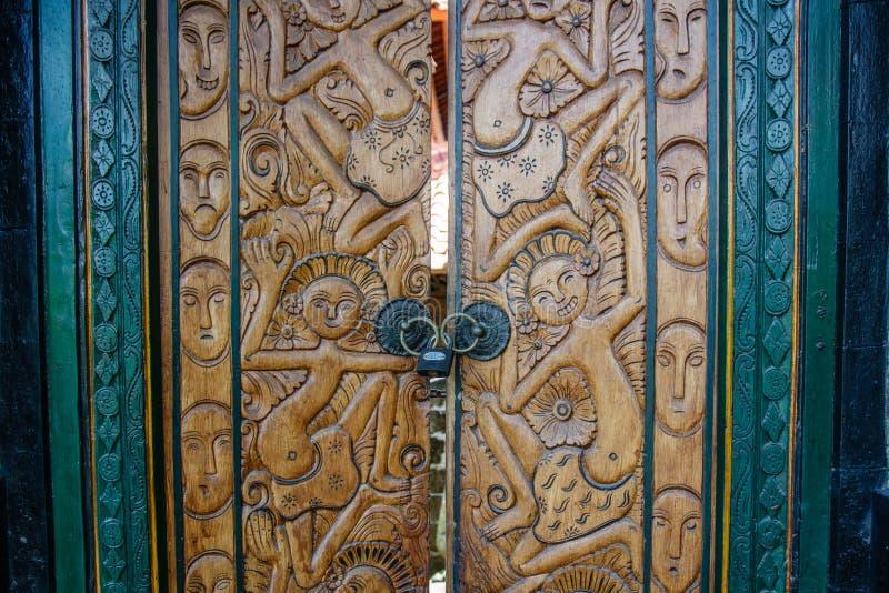 巴厘语房子,巴厘岛,印度尼西亚的被雕刻的木门 免版税库存照片