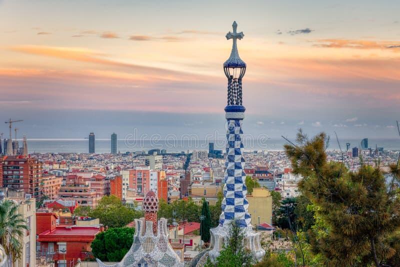 巴塞罗那看法从公园Guell的日落的 在前景,正门大厦的五颜六色的屋顶的细节 免版税库存照片