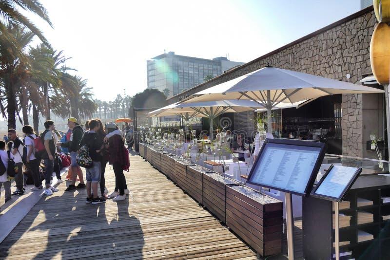 巴塞罗那西班牙沿海岸区酒吧和餐馆大阳台透视图与游人用餐的 库存照片