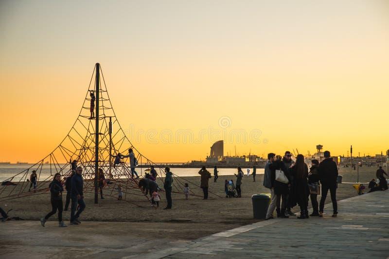 巴塞罗那,西班牙- 05 12 2018年:在巴塞洛内塔海滩的美好的日落在孩子的一种绳索操场设备附近 免版税库存图片