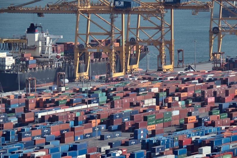 巴塞罗那,西班牙- 2018年5月,27:在货船被装载的蓝色和红色金属货箱由巨大的港起重机在海港 免版税图库摄影
