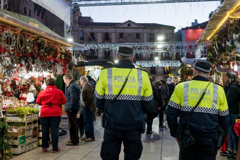 巴塞罗那,西班牙- 2018年12月19日:加泰罗尼亚和西班牙武装的警察巡逻圣诞节市场作为恐怖分子的预防 库存图片