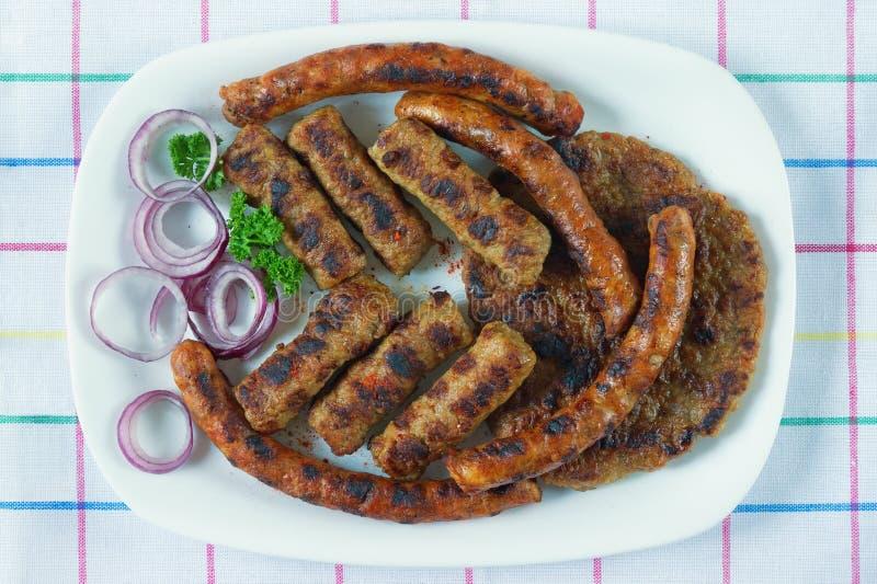 巴尔干烹调 Cevapi、kobasica和pljeskavica -肉末烤盘  平的位置 库存图片