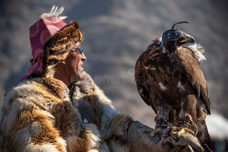 巴彦Ulgii地区,蒙古西部- 2018年10月07日:游牧人比赛,金鹰节日 戴举行A的眼镜的黑黝黝的猎人 免版税库存图片