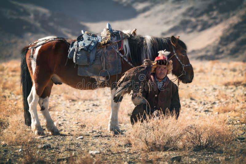 巴彦Ulgii,蒙古西部- 2018年10月07日:游牧人比赛,金鹰节日 蒙古游牧人猎人坐背景 免版税库存图片