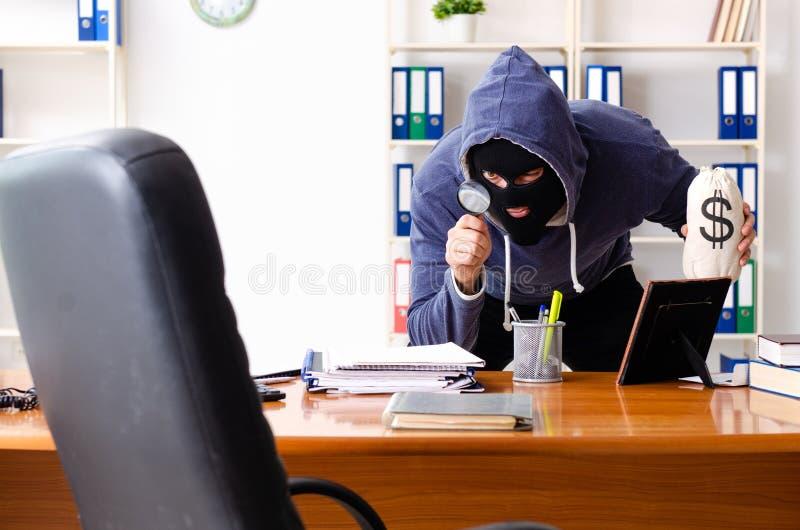 巴拉克拉法帽的男性窃贼在办公室 免版税图库摄影