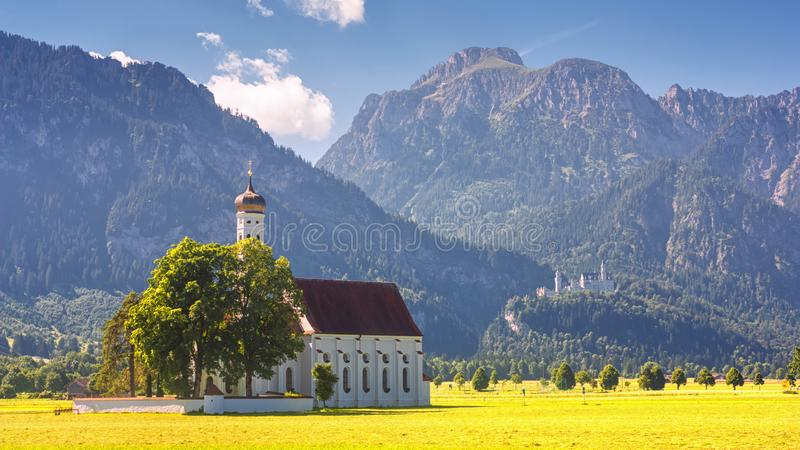 巴法力亚风景-圣Coloman教会的看法在高山山和新天鹅堡城堡的背景的 库存图片