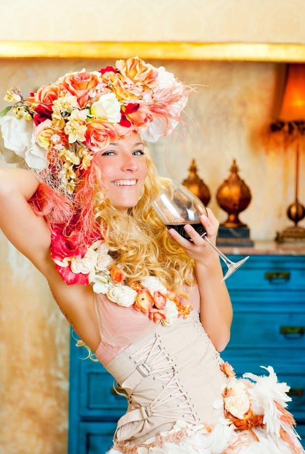巴洛克式的喝红葡萄酒的方式白肤金发的womand 库存照片