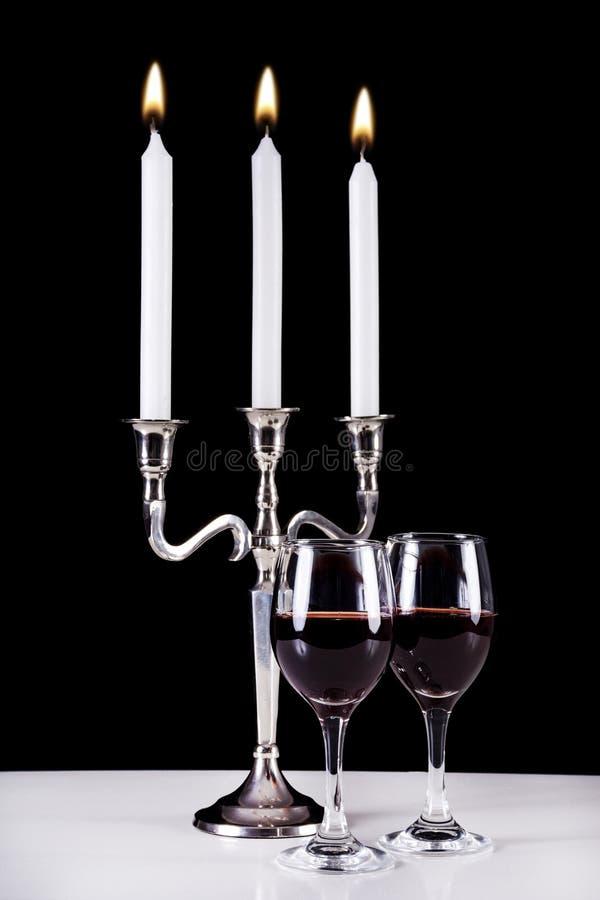 巴洛克式的烛台和两块红葡萄酒玻璃在白色书桌上 免版税库存图片