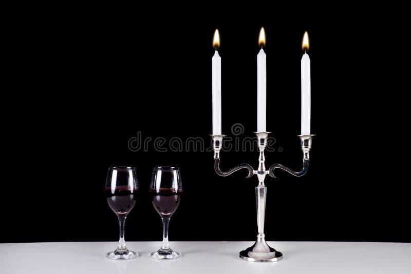 巴洛克式的烛台和两块红葡萄酒玻璃在白色桌上 库存图片