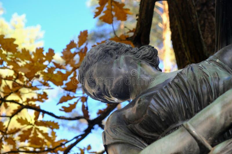 巴甫洛夫斯克,俄罗斯- 2018年10月11日-与老妇人雕象的美好的秋天好日子在巴甫洛夫斯克公园,黄色和棕色 免版税库存照片