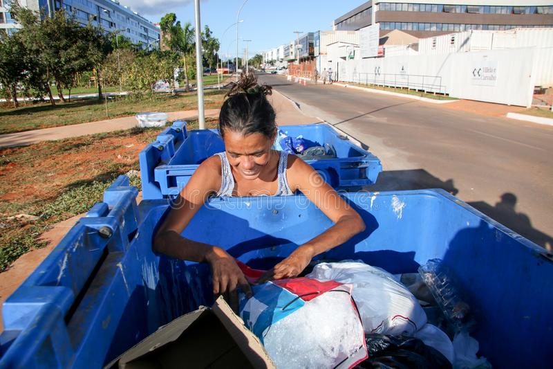 巴西利亚,D f 巴西2019年6月11日:开掘通过垃圾的一个可怜的夫人在一个富有邻里尝试和赢得某一mone 免版税库存图片