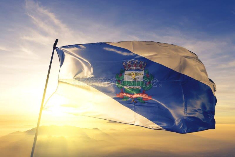 巴西国旗里贝拉奥·普雷图在日出雾霭的顶端挥舞 免版税库存图片