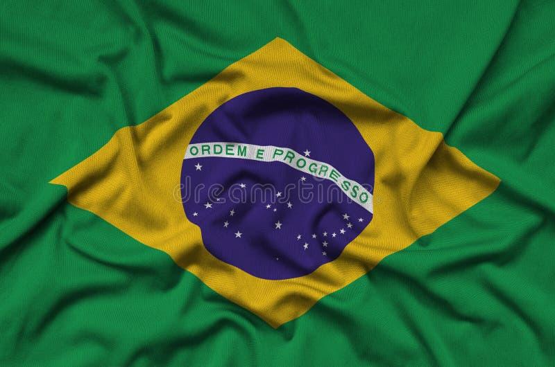 巴西旗子在与许多折叠的体育布料织品被描述 体育队横幅 库存照片