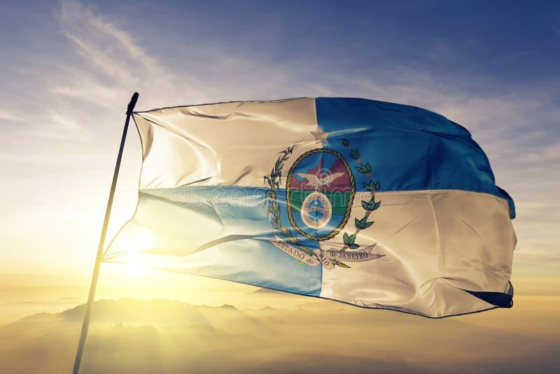 巴西旗子纺织品挥动在顶面日出薄雾雾的布料织品里约热内卢状态  皇族释放例证