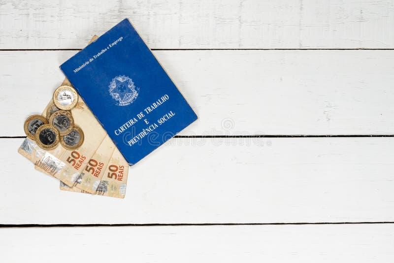 巴西金钱纸币、巴西硬币和工作许可在白色 免版税库存图片