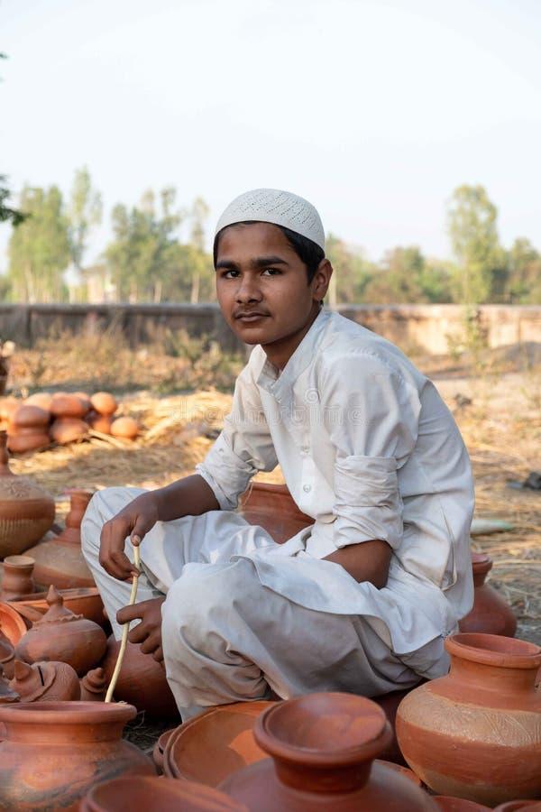 巴达尔萨,北方邦/印度4月3,2019:卖瓦器姿势的男孩为照片在围拢Nandigram Bharatkund的节日 免版税图库摄影