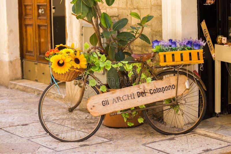 巴里,意大利- 2018年7月11日,一条狭窄的街道的看法在巴里的中心 用花装饰的一辆老自行车商店外 库存图片