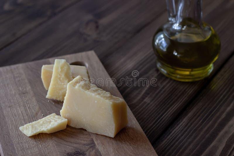 巴马干酪和橄榄油 背景棕色木 库存照片