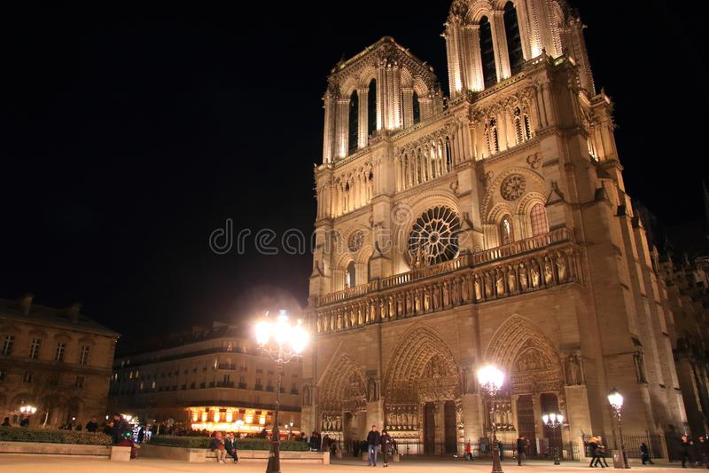 巴黎圣母院在巴黎和它的与游人的照明设备在晚上 免版税库存图片