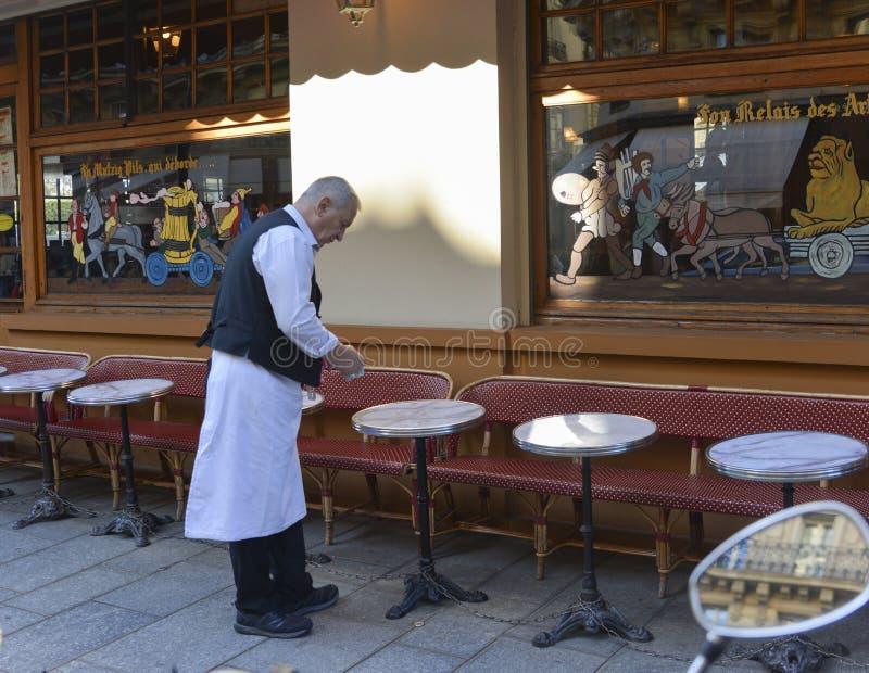 巴黎,法国- 2016年10月16日:一位年长侍者以传统形式在著名附近清洗在传统巴黎人咖啡馆的桌 免版税库存图片