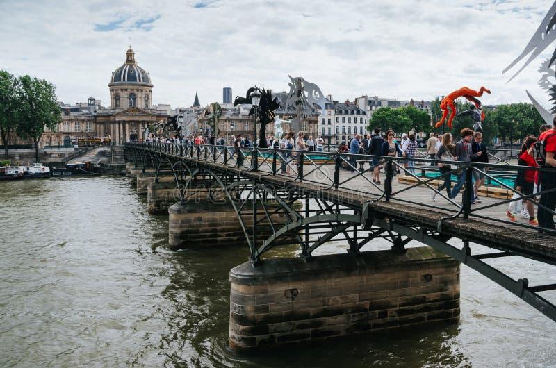 巴黎,法国- 2016年6月25日:人们走在艺术桥的,有当代雕象和设施的桥梁 库存照片