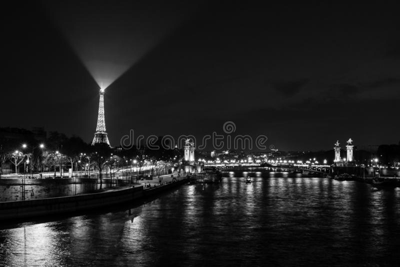 巴黎,法国- 2019年4月1日:埃菲尔铁塔的全景在巴黎在有小船的塞纳河在晚上 图库摄影