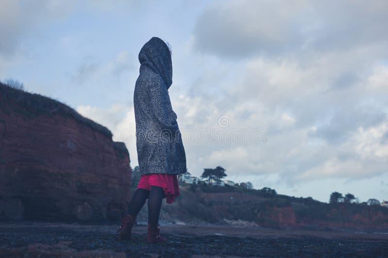 戴头巾外套的少妇走在海滩的 图库摄影