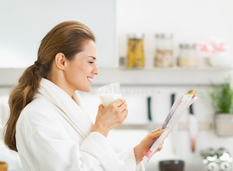 浴巾饮用奶和读杂志的主妇 库存照片
