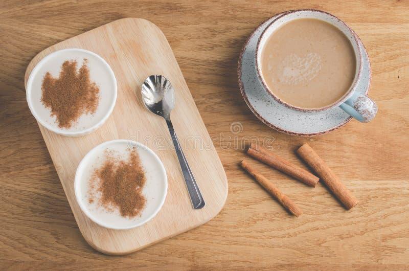 布丁用桂香和一杯咖啡/布丁用桂香在一个木盘子和一杯咖啡 r 免版税图库摄影