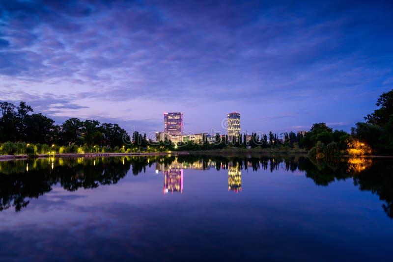 布加勒斯特办公楼在与湖反射的蓝色小时在夏时,罗马尼亚 免版税图库摄影
