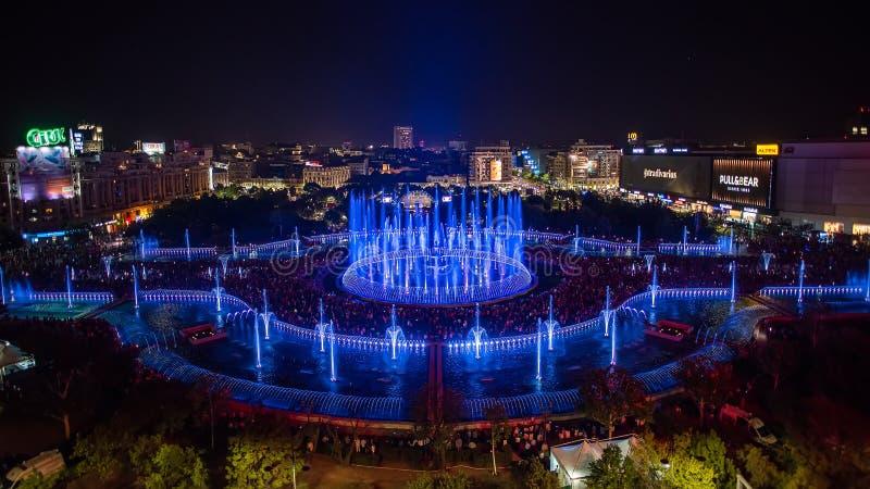 布加勒斯特市中央Unirii方形的新的2018年喷泉全景和夜城市地平线 免版税库存图片